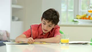 Hispanic Boy Doing Homework On Kitchen Counter