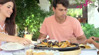 Hispanic Family Eating Paella At Home Together
