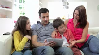 Hispanic Family Sitting On Sofa With Digital Tablet