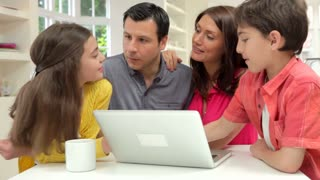 Hispanic Family Using Laptop At Home