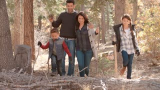 Hispanic family walking in a forest, close up front view