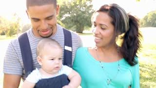 Hispanic Family With Baby In Carrier Walking Through Park