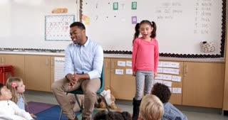 Hispanic schoolgirl standing with teacher in front of class