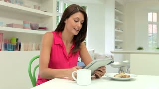 Hispanic Woman Using Digital Tablet In Kitchen At Home