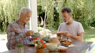 Homosexual Couple At Home Eating Meal On Outdoor Verandah