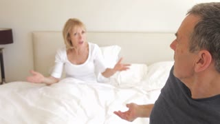 Husband sits on the end of bed arguing with wife who is still in bed.Shot on Canon 5D Mk2 at at a frame rate of 30 fps