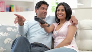 Indian Couple Sitting On Sofa Watching TV Together