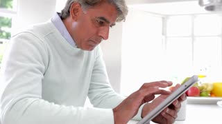 Indian Man Using Digital Tablet In Kitchen At Home
