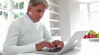 Indian Man Using Laptop Computer In Kitchen At Home