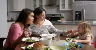 Lesbian couple and daughter having dinner in their kitchen, shot on R3D