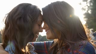 Lesbian couple embrace touching noses, eyes closed, close up