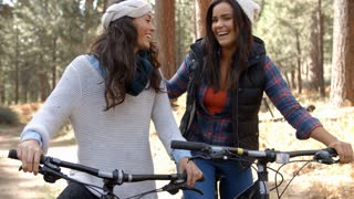 Lesbian couple embracing on bikes in a forest, close up