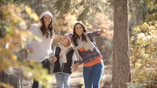 Lesbian couple walking in a forest with their daughter