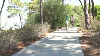 Long shot of romantic senior couple cycling along country path towards camera.Shot on Canon 5D Mk2 at at a frame rate of 30 fps