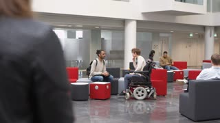 Low angle view of students in a busy university lobby area, shot on R3D