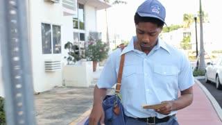 Mailman Walking Along Street Delivering Letters