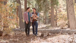 Male couple in forest with baby in sling walk towards camera