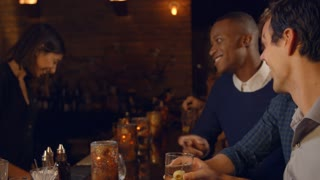 Male Friends Enjoying Night Out At Cocktail Bar, Slow Motion