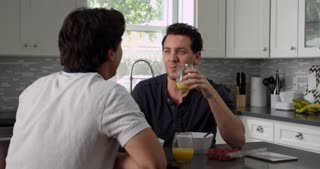 Male gay couple talking at breakfast in their kitchen, shot on R3D