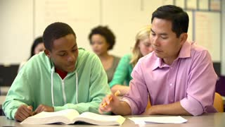 Male High School Student With Teacher Discussing Textbook