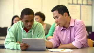 Male High School Student With Teacher Using Digital Tablet