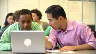 Male High School Student With Teacher Using Laptop