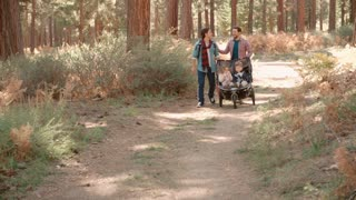 Male parents pushing stroller with two kids through a forest