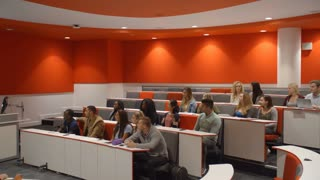 Male teacher in lecture theatre presenting to students