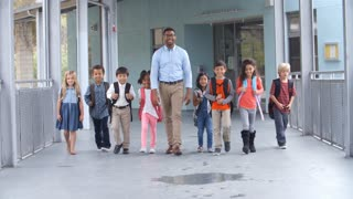 Male teacher walking in corridor with elementary school kids
