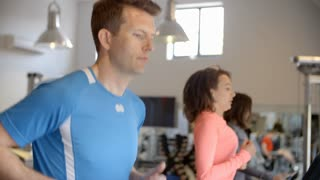 Man and two young women running on treadmills at a gym