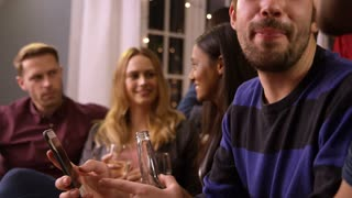 Man Checking Mobile Phone At Party With Friends
