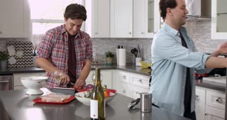 Man chopping while his boyfriend cooks ingredients in a pan, shot on R3D