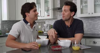 Man feeds his partner a berry and checks tablet at breakfast, shot on R3D