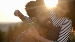 Man Giving Woman Ride On Back Against Setting Sun