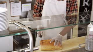 Man slicing bread behind the counter of a sandwich bar, shot on R3D