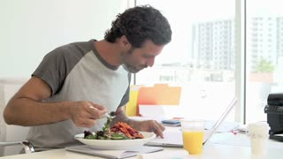 Man Working In Design Studio Having Lunch At Desk