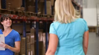 Manager And Worker Checking Goods In Warehouse