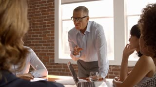 Mature Businessman Standing To Address Boardroom Meeting