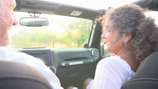 Mature Couple Driving Along Country Road In Open Top Car