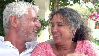 Mature Couple Sitting Outdoors In Garden Together