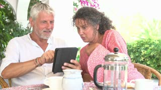 Mature Couple Using Digital Tablet At Breakfast Table