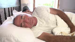 Mature Couple Waking Up In Bed In Morning