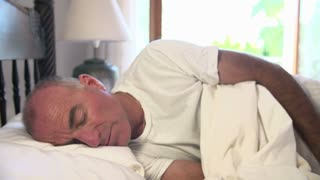Mature Man Waking Up In Bed In Morning