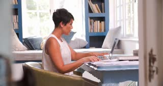 Mature Woman At Desk Working In Home Office With Laptop
