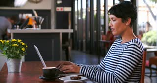 Mature Woman In Cafe Working On Laptop And Answering Phone