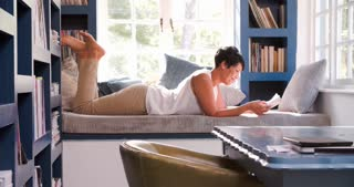 Mature Woman Lying On Couch At Home Reading Book