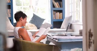 Mature Woman Sitting At Desk Reading Book In Home Office