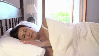 Mature Woman Sleeping In Bed During Day