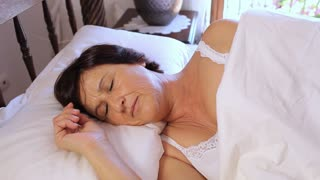 Mature Woman Waking Up In Bed In Morning