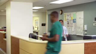 Medical Staff Working At Busy Nurses Station